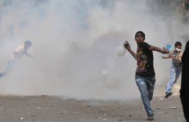 An anti-Mursi protester runs to throw a tear gas canister back during clashes with riot police at Tahrir square in Cairo