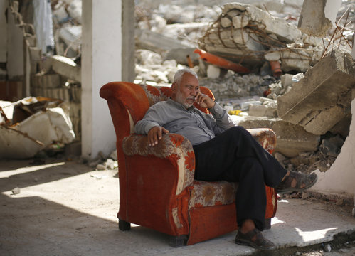 Palestinian man sits in a couch near the remains of his house that witnesses said was destroyed by Israeli shelling during a 50-day war last summer, in Biet Hanoun town