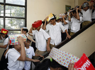 Students use make shift protective head gear and books to cover their heads as they leave a building during an earthquake drill at San Juan elementary school in San Juan