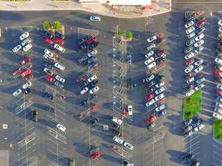 Top view parking lots with rows of parked car, shopping carts, road sign for disabled drivers ata supermarketin Houston, Texas, USA at sunset. Urban infrastructure and transportation concept