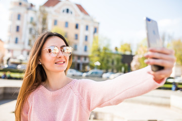 Young girl take selfie from hands with phone on summer city street. Urban life concept.