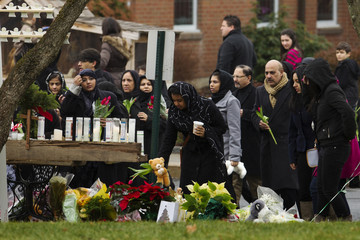 Mourners place flowers, stuffed animals, and candles at a memorial in front of the St. Rose of Lima Catholic church in Newtown, Connecticut