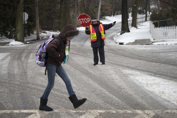 A guard helps a student cross an intersection after schools closed early ahead of bad weather in Pelham, New York