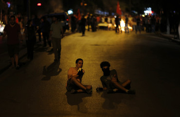 Anti-government protesters sit on a road during a demonstration in Ankara