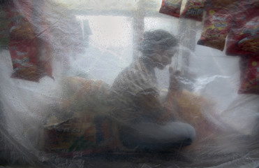 A girl sits inside a roadside eatery covered with polythene during rain showers in Noida