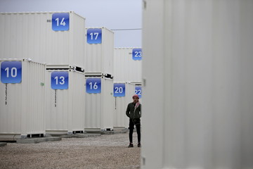 A migrant walks amidst shipping containers converted into homes at a state-run shelter near Calais, northern France