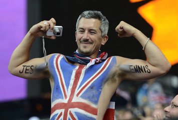 A spectator with a Union flag painted on his body flexes his muscles as he cheers for Britain's heptathlete Jessica Ennis before the heptathlon shot put competition during the London 2012 Olympic Games at the Olympic Stadium