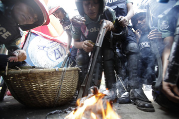 Police officers inhale smoke from paper set on fire, which they believe will protect them from tear gas during a clash with different Islamist parties in Dhaka