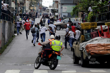 People run away from police (on motorcycle) during riots for food in Caracas