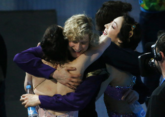 Virtue and Moir hug Davis and White hug before the flower ceremony during the Figure Skating Ice Dance Free Dance Program at the Sochi 2014 Winter Olympics