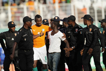 Stadium security escort an Ivory Coast fan off the pitch during their African Nations Cup qualifying soccer match against Sierra Leone at the Felix Houphouet Boigny stadium in Abidjan