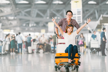 Young Asian tourist couple happy and excited together for the trip, girlfriend sitting and cheering on baggage trolley or luggage cart. Holiday vacation travelling abroad concept, with copy space