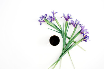 Cup of coffee and purple iris flowers on white background. Flat lay, top view.