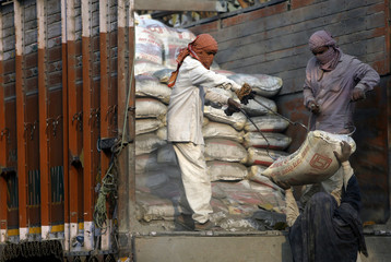 Workers unload cement bags from a truck near the construction site of residential buildings in New Delhi