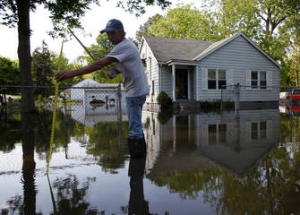Arthur Burton measures encroaching water as floodwaters slowly rise in Memphis, Tennessee