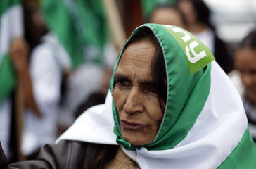 A woman covers her head with a flag of the National Liberation Party during a campaign rally in Alajuelita