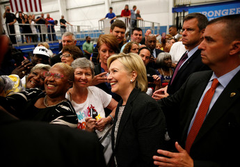 U.S. Democratic presidential nominee Hillary Clinton smiles as she takes pictures with supporters at Futuramic Tool & Engineering in Warren
