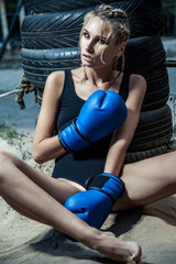 Fashion boxer woman in a black sportswear and with blue boxing gloves. outdoor workout of young blonde woman.