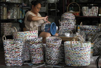 A worker from the Risen Christ Parish Multi-Purpose Cooperative uses a pail as a base while weaving strips of recycled newspapers and magazines to form a basket in Tondo city, metro Manila