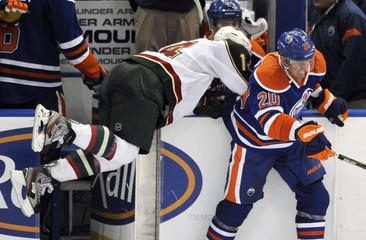 Wild's Powe is hit by Oilers' Belanger during their NHL hockey game in Edmonton