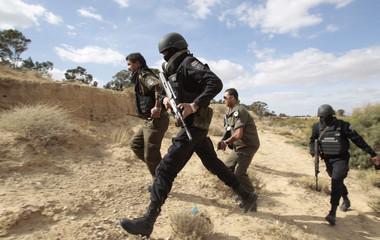 Tunisian police run as they patrol a mountain in Kasserine