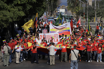 Supporters of Venezuela's President Hugo Chavez carry flags during a march in Havana