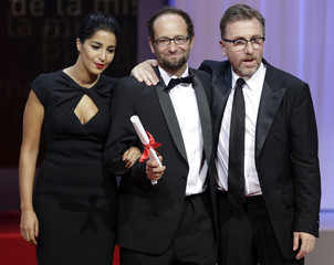 Best director award winner Reygadas for the film  Post Tenebras Lux reacts next to Roth and Bekhti during the awards ceremony of the 65th Cannes Film Festival