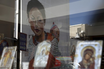 Street mural depicting a Nepalese woman with a baby on her back by Greek street artist Achilleas Michaelides, alias 'Paparazzi', is reflected in a shop window in which Greek Orthodox icons are displayed in the coastal town of Limassol, Cyprus