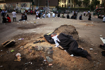 Man sleeps during a sit-in at Tahrir Square, after a court sentenced deposed president Hosni Mubarak to life in prison, in Cairo