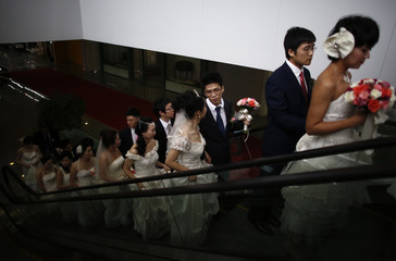 Couples arrive at a staged mass wedding, organised as part of a matchmaking event to inspire singles to get married, in Shanghai