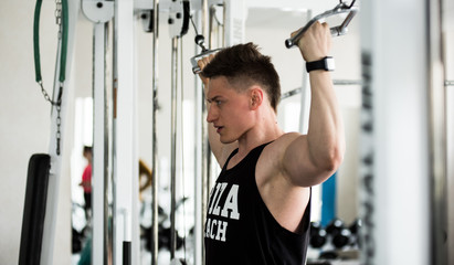 Strong muscular male sportsman working out in gym with trainers. A fitness instructor doing exercises. Fitness club gym training lifestyle commercial concept.