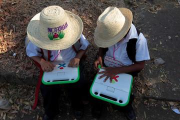 Schoolchildren use their XO laptops at the Municipal Stadium in Ciudad Sandino