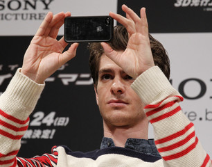 "Andrew Garfield takes a picture at a news conference to promote his film ""The Amazing Spider-Man"" in Tokyo"