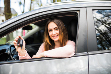 Young woman near the car with keys in hand while buying car