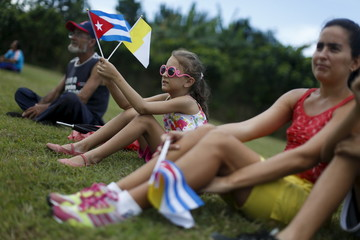 A girl holds Cuban and Vatican flags while waiting for the arrival of Pope Francis outside the airport in Havana
