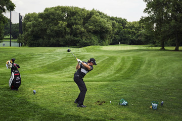 Golfer McIlroy of Northern Ireland takes a swing while teaching the proper stance during a golf clinic for children in New York