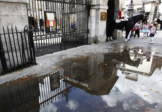 A member of the Queen's Life Guard cavalry is reflected in a puddle while standing on duty in Whitehall in central London