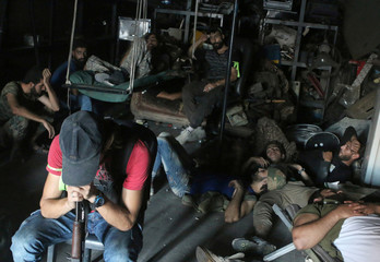 A file photo shows Free Syrian Army fighters resting inside a mechanic shop in Ramousah area southwest of Aleppo