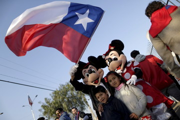 Fans take a picture with an official mascot of The Walt Disney Company before the Copa America semi-final soccer match between Chile and Peru at the National Stadium in Santiago, Chile