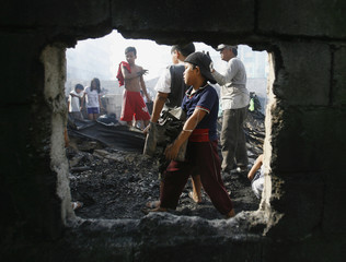 Residents search through charred houses after a fire swept through a slum community in Quezon City, Metro Manila