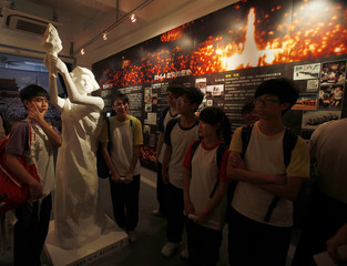 Students pose with a statue of the Goddess of Democracy as they visit a a residential block in Hong Kong