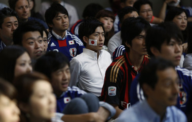 Japan's soccer fans watch the team's 2014 World Cup Group C soccer match against Greece on a big screen during a public viewing event in Tokyo