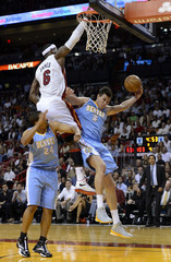 Miami Heat's LeBron James defends Denver Nuggets' Andre Miller and Danilo Gallinari during the second half of their NBA basketball game in Miami