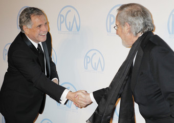 Director and producer Steven Spielberg reaches out to shake hands with Leslie Moonve as they arrive in Beverly Hills