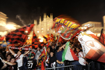 AC Milan's soccer fans celebrate after the team won the Serie A title against AS Roma in Duomo square, downtown Milan