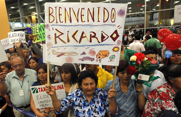 "The relatives of Ricardo Benites await his arrival while holding a sign that reads ""Welcome back Ricardo"" at the airport in Lima"