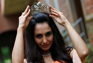 Syrian refugee Bahno holds a crown during the preparation for the crowning ceremony to the Trier wine queen in Trier