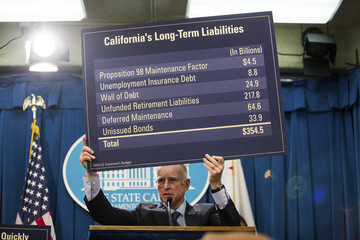California Governor Brown holds up details of the state's long-term liabilities to answer a reporter's question during a news conference to unveil his proposed 2014-15 state budget in Sacramento