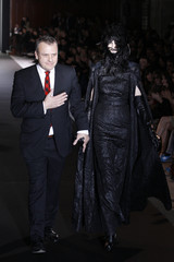 French designer Jean-Charles de Castelbajac appears with a model at the end of his Fall/Winter 2012-2013 women's ready-to-wear fashion show in Paris