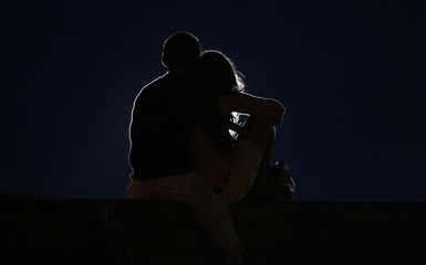 A couple embraces, silhouetted by a spotlight, at a prayer vigil ceremony for the 19 firefighters killed in the nearby Yarnell Hill wildfire in Prescott